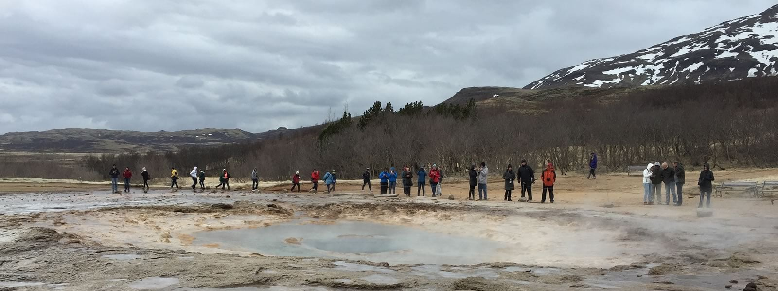 G3 students gather in front of a steamy pond on a field excursion to witness a geyser.